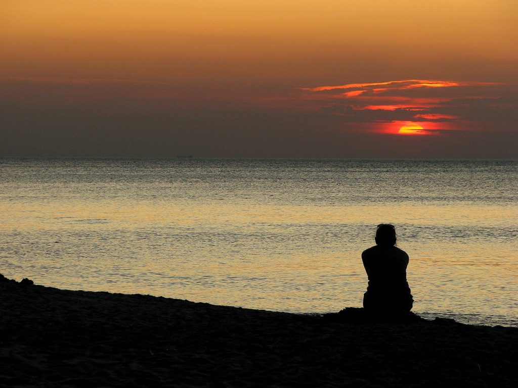 person sitting alone at sunset